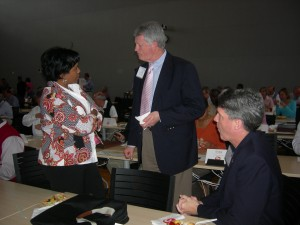 Community Foundation's Lesley Grady and ACCG's Ross King listed to Jack Smith, chairman of Fayette County (standing)