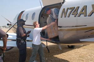 Peter J. Anderson, senior partner with Sutherland asbill and the treasurer for ServeHaiti, unloads boxes from the plane with Sanders' help. A U.S. Customs agent is looking on.